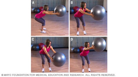 Photo of woman doing squat and reach exercise with fitness ball