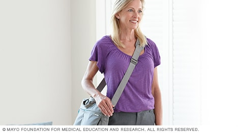 Photo of a woman carrying a large purse by its shoulder strap across her body.