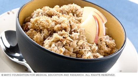 Bowl of oatmeal topped with wheat germ and apple slices
