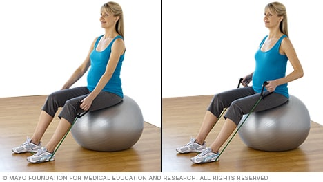 Pregnant woman practicing seated row with resistance tubing