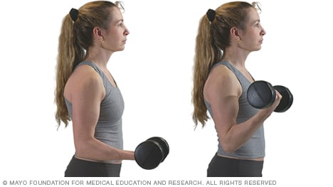 Photo of woman doing biceps curl with dumbbell