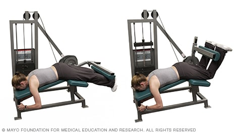 Photo of woman doing hamstring curl with weight machine