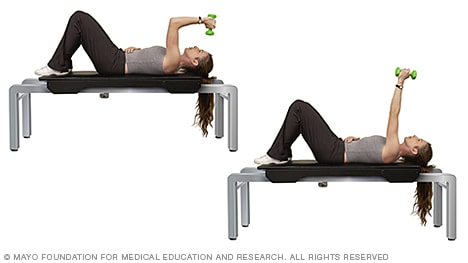 Photo of woman doing triceps extension with dumbbell
