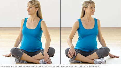 Pregnancy stretches — pregnant woman practicing torso rotation