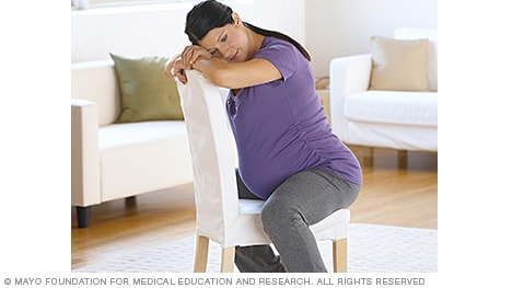 Image of woman in labor leaning forward against a chair