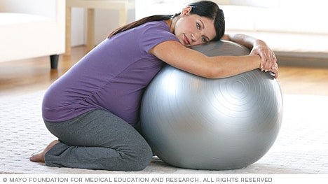 Image of a pregnant woman kneeling with birthing ball