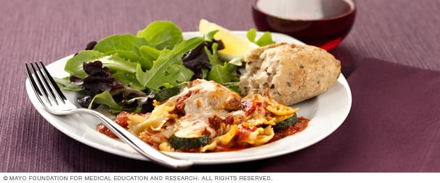 Photo of baked pasta with zucchini, salad and roll