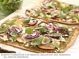 Photo of pizza with herbs, onions and feta